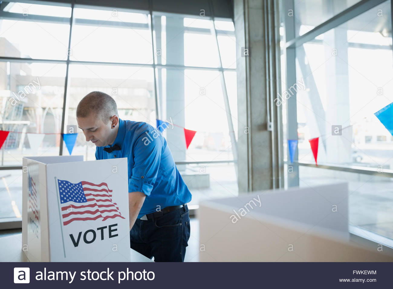 Man bow tie in voting booth polling place - Stock Image