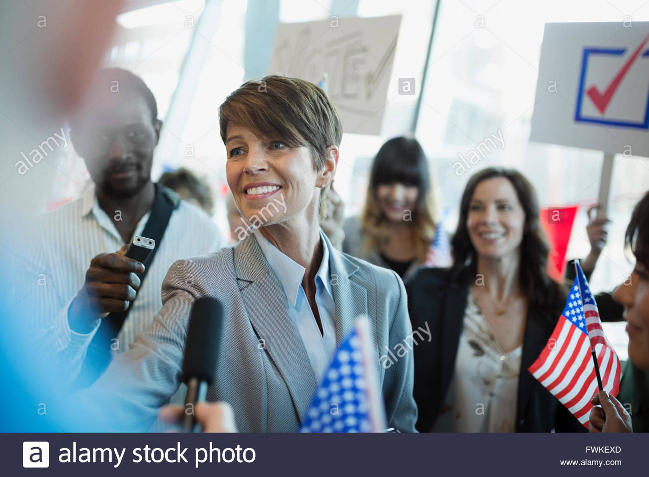 Smiling female politician greeting media and audience - Stock Image