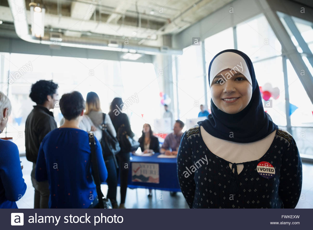 Portrait smiling young woman hijab voter polling place - Stock Image