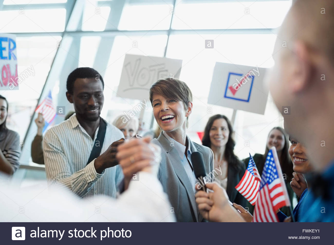 Enthusiastic female politician shaking hands with audience - Stock Image