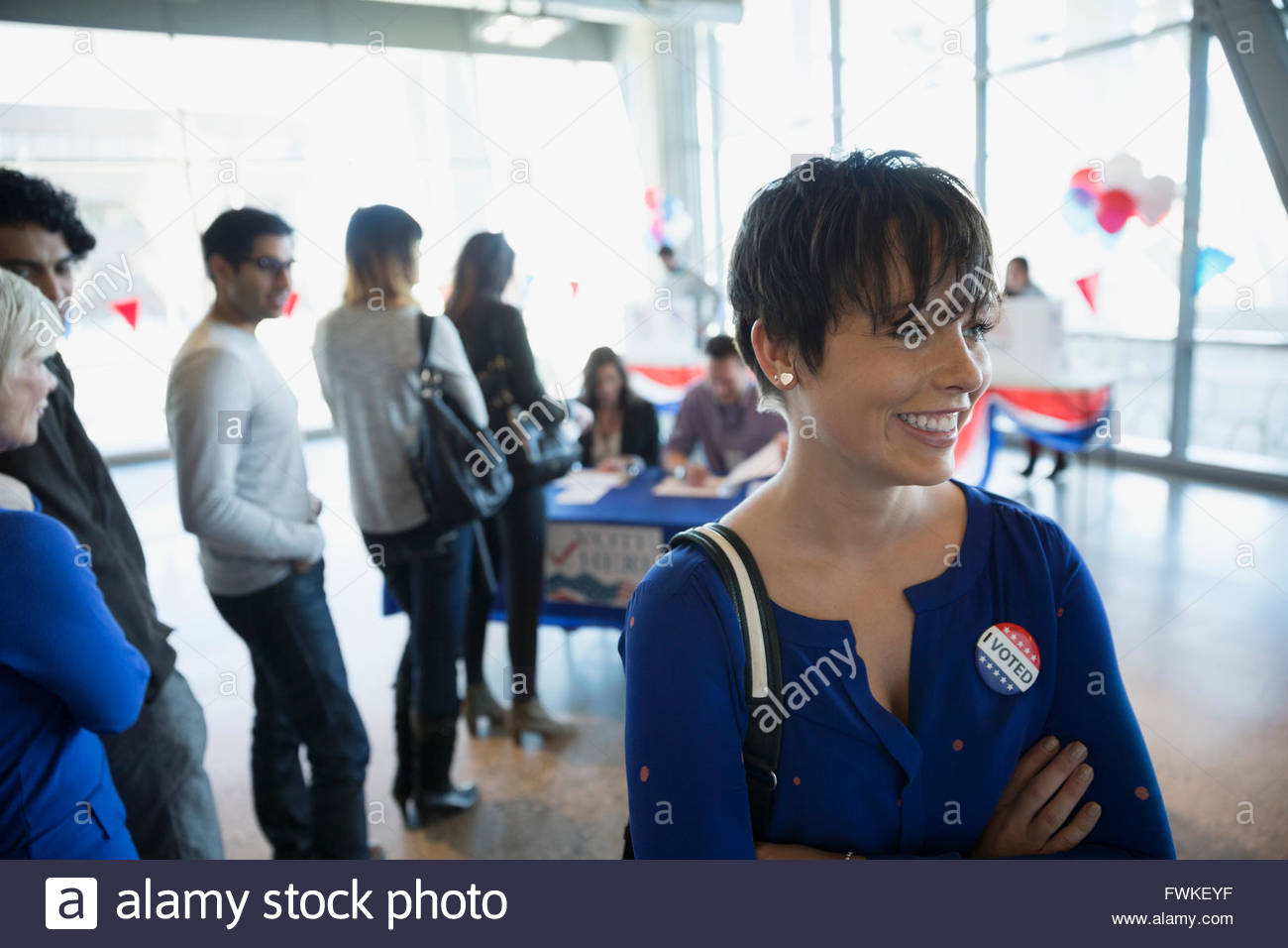 Smiling young woman at voter polling place - Stock Image