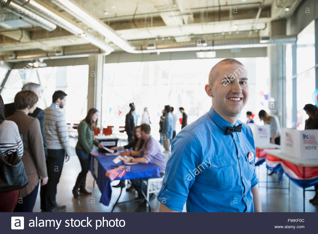 Portrait smiling man bow tie voter polling place - Stock Image