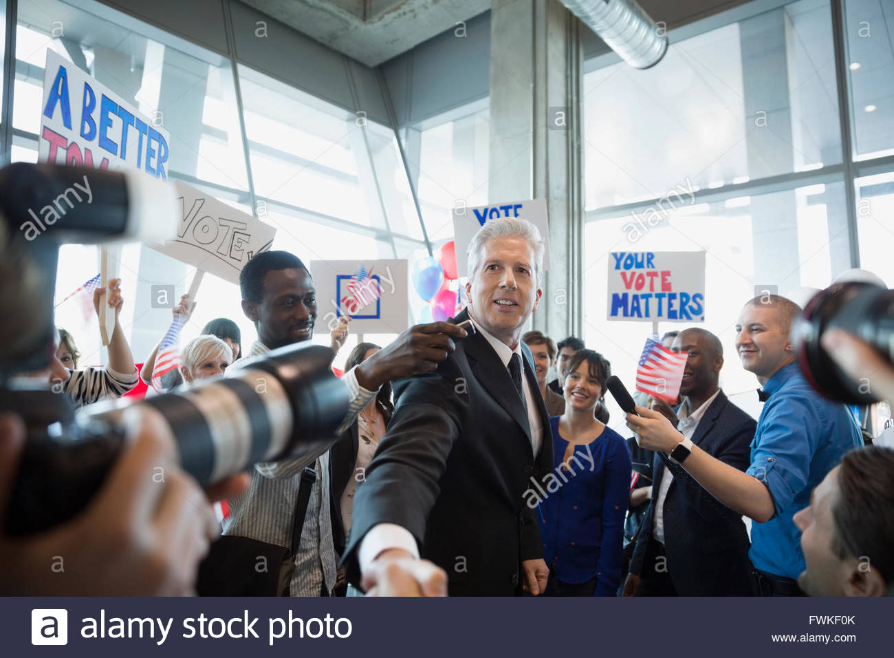 Politician shaking hands with crowd at political rally - Stock Image