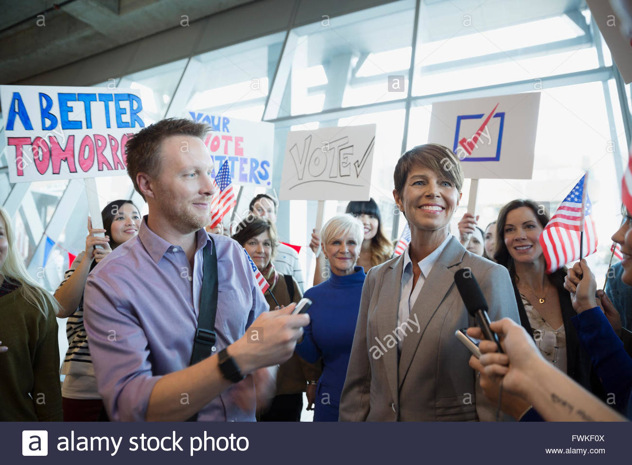 Female politician being interviewed among crowd at rally - Stock Image