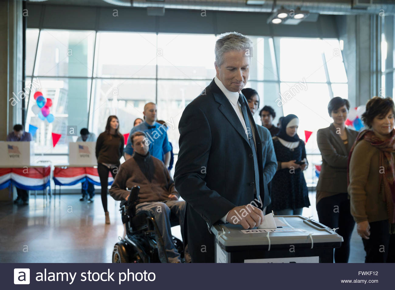 Voter placing ballot in ballot box polling place - Stock Image
