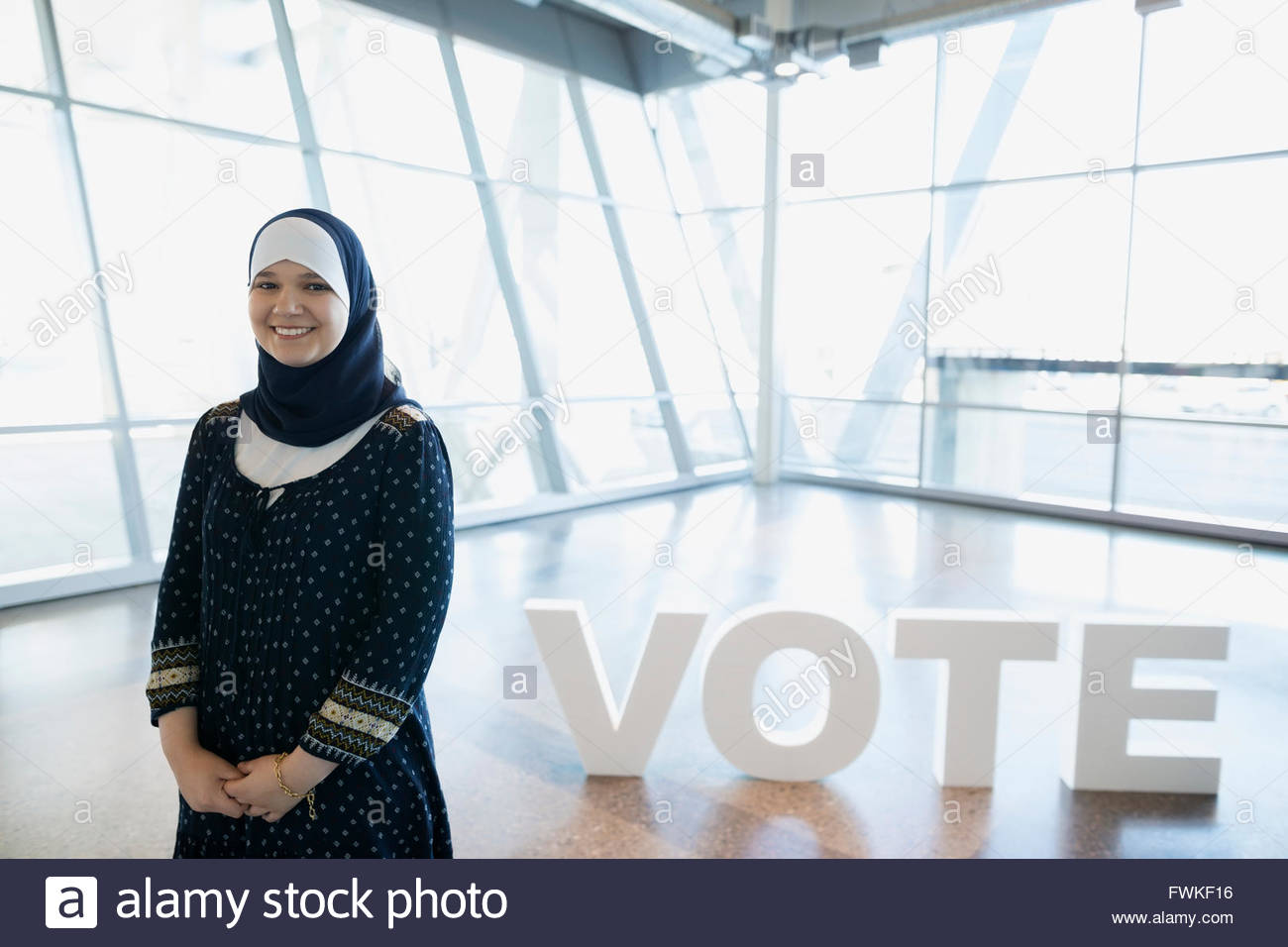 Portrait smiling young woman hijab near Vote text - Stock Image