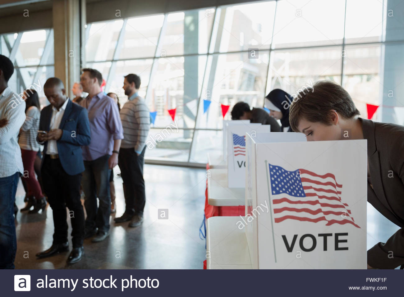 Young woman in voting booth at polling place - Stock Image