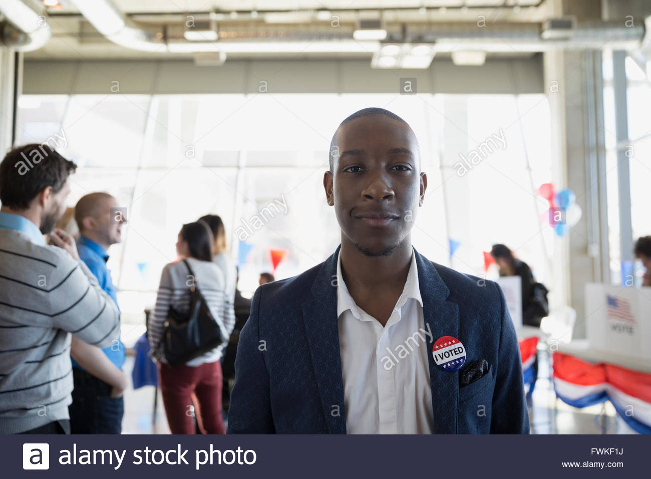 Portrait confident young man at voter polling place - Stock Image