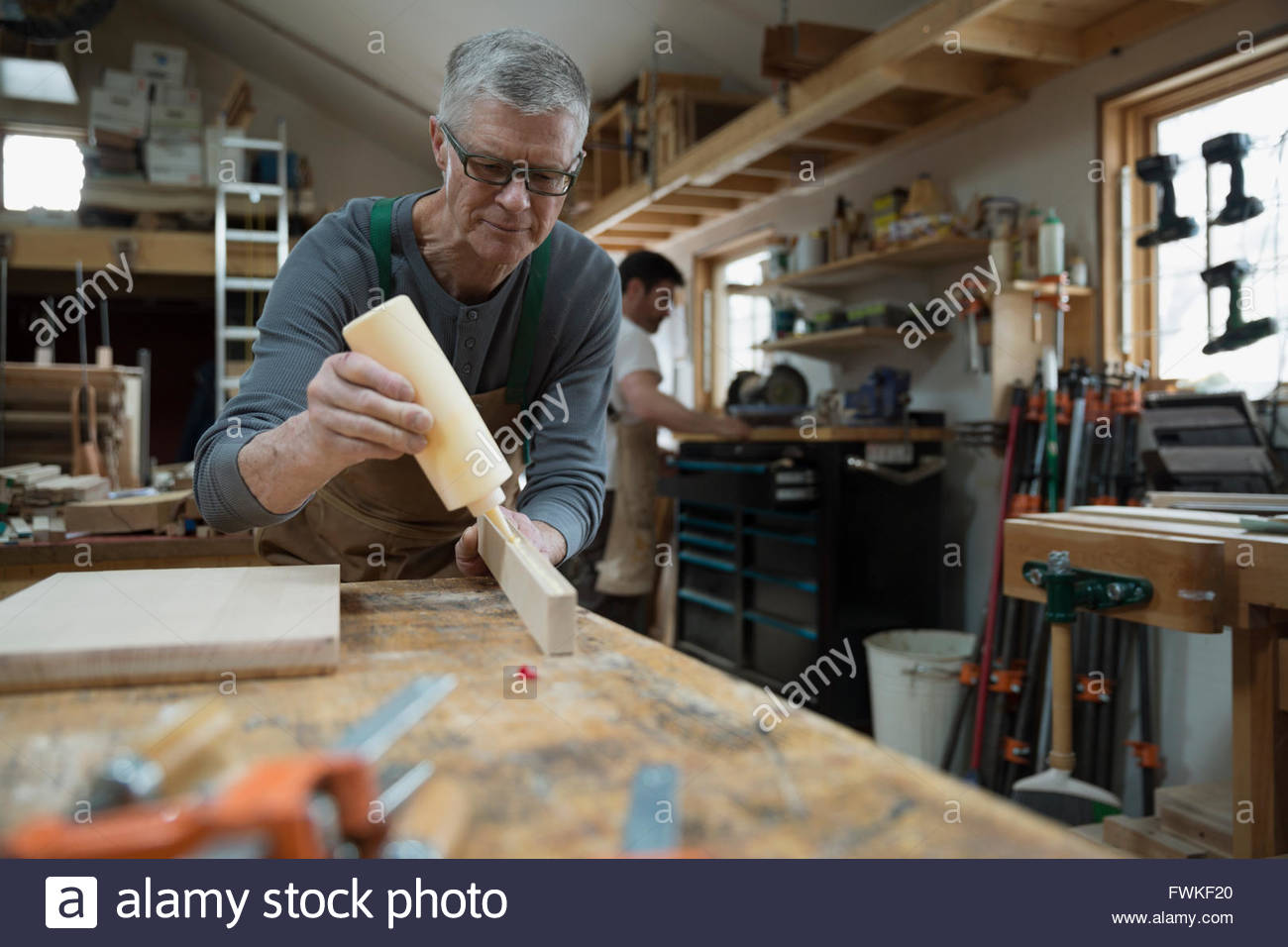 Carpenter gluing wood piece in workshop - Stock Image
