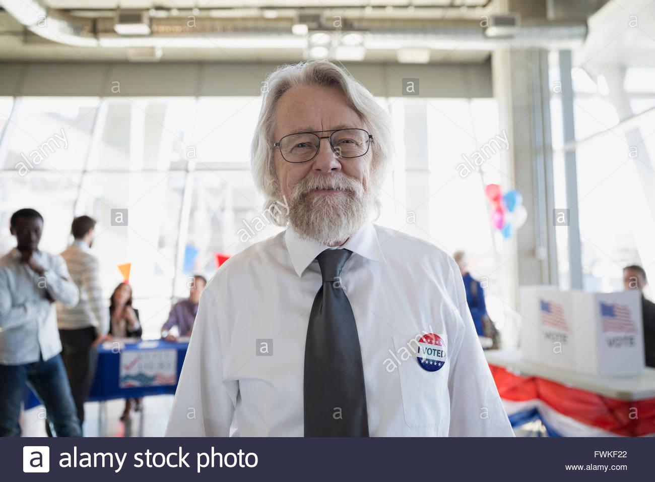 Portrait smiling senior man at voter polling place - Stock Image