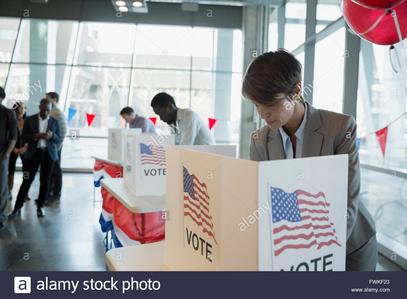 Woman in voting booth at polling place - Stock Image