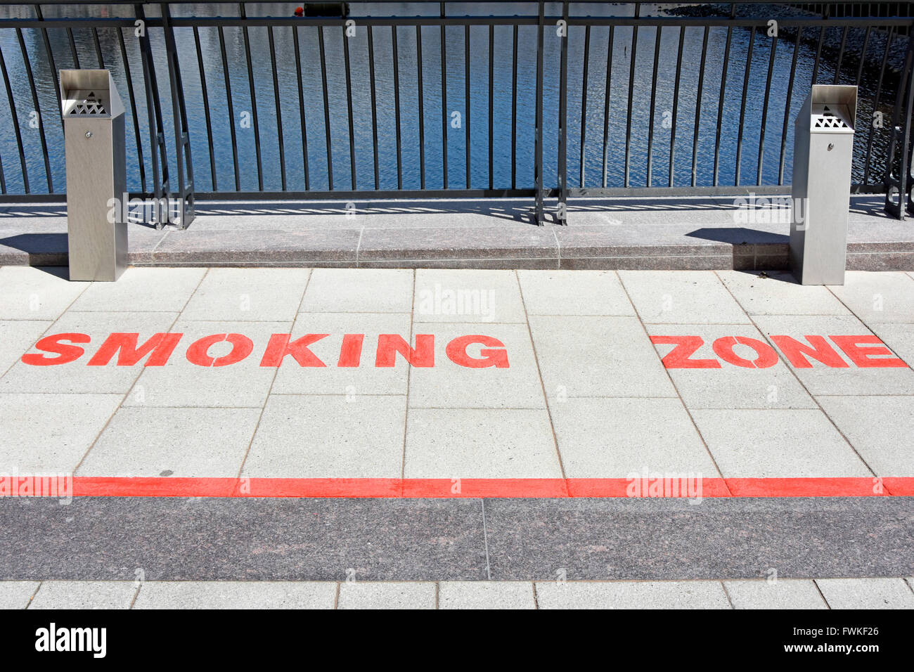 Pavement markings designated Smoking Zone in open space amongst office blocks at Canary Wharf London Docklands Isle - Stock Image