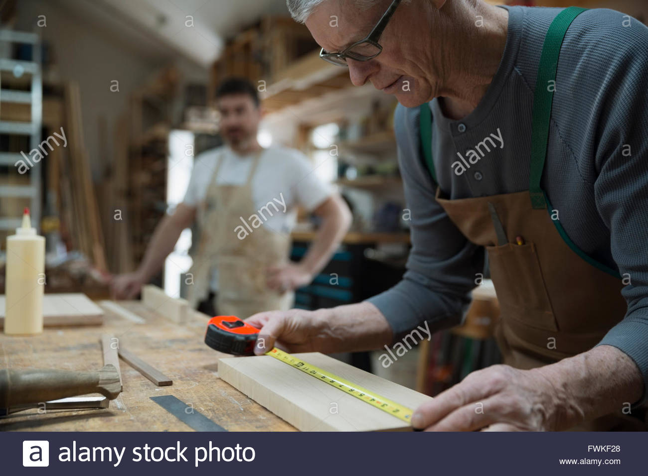 Carpenter measuring wood piece in workshop - Stock Image