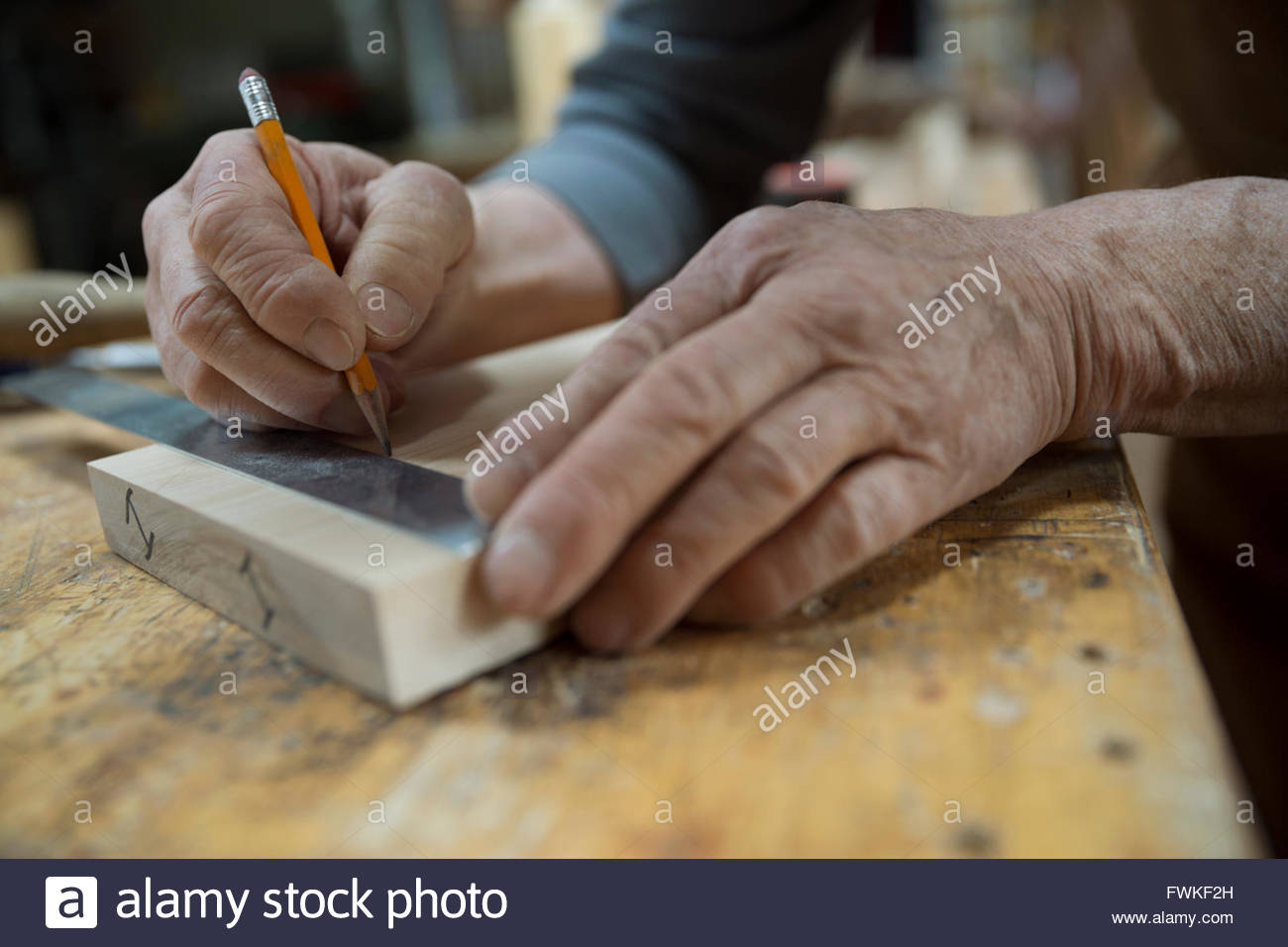 Close up carpenter measuring and marking wood piece - Stock Image
