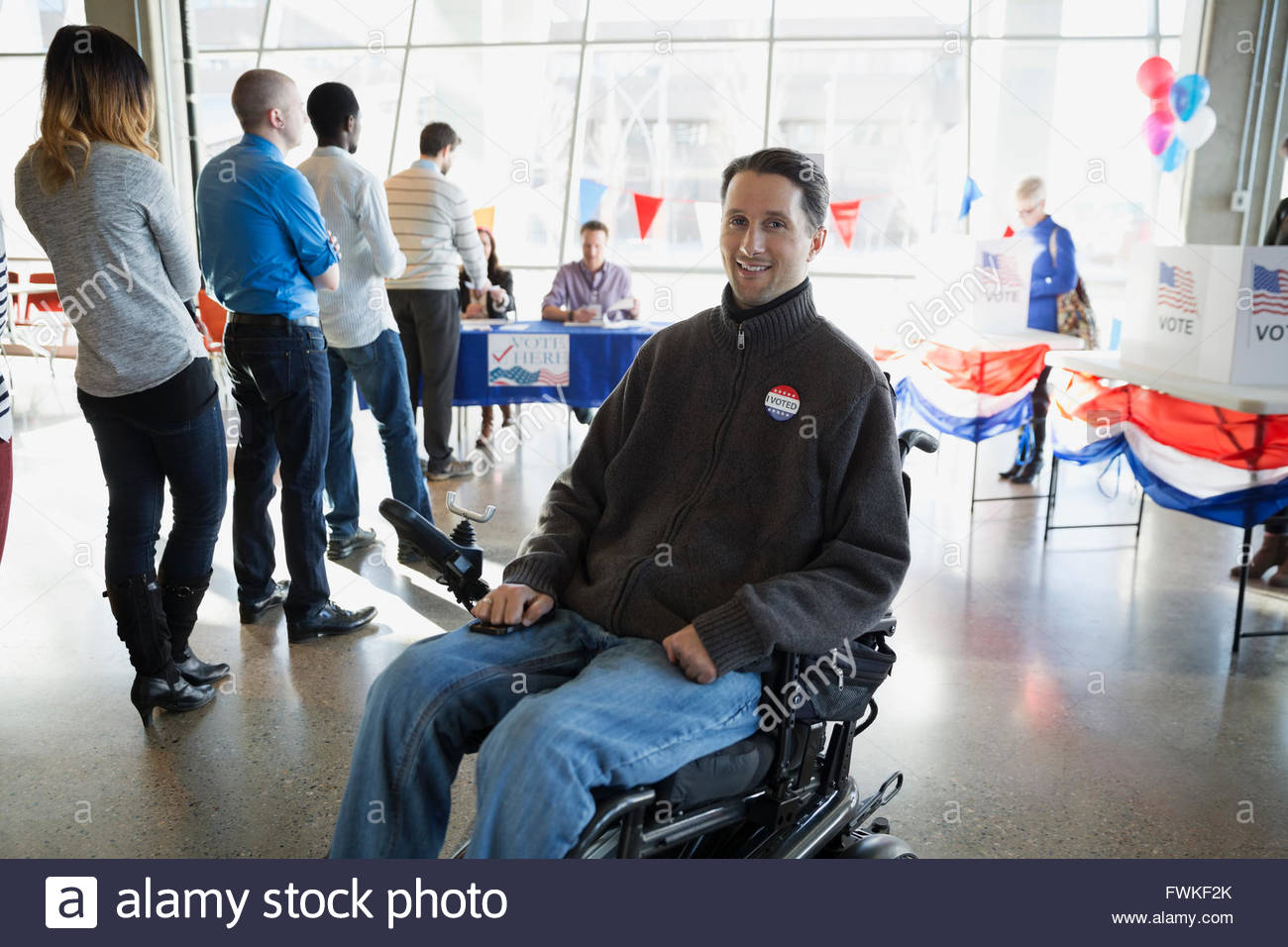 Portrait smiling man wheelchair at voter polling place - Stock Image
