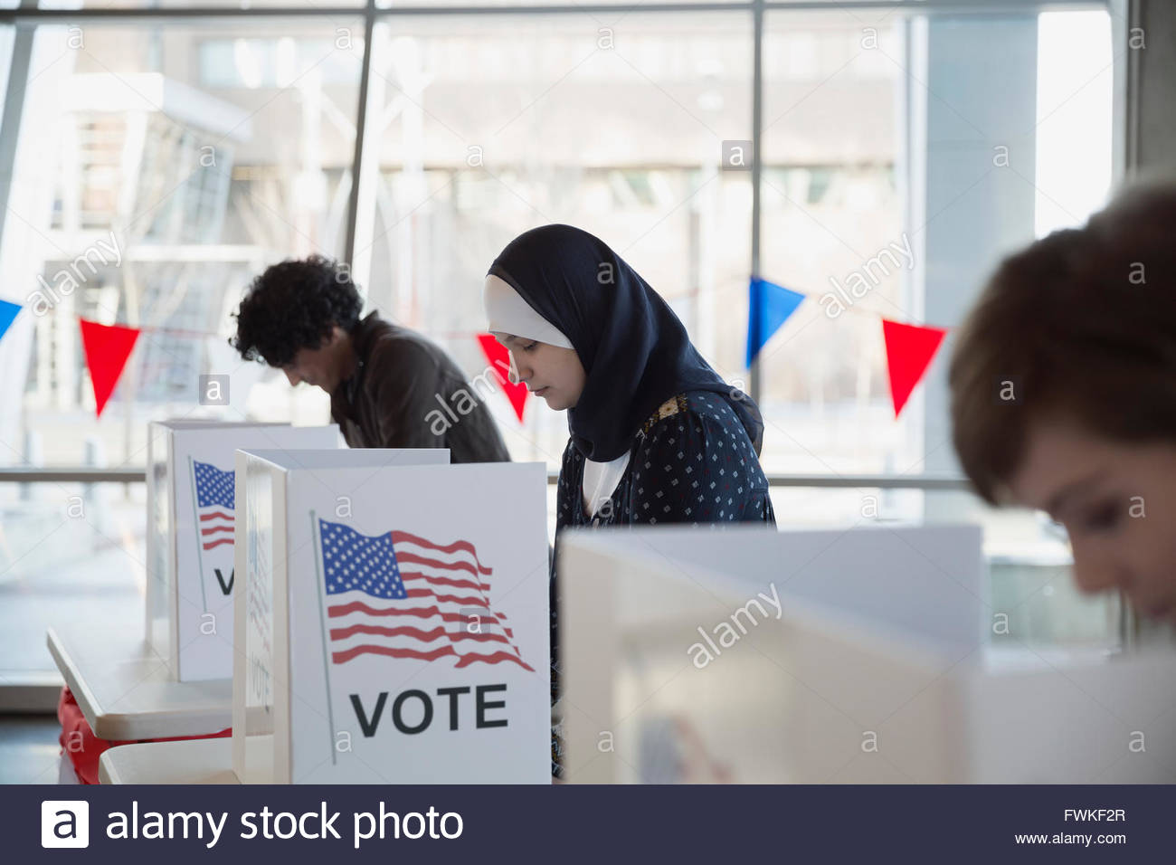 Woman in hijab in voting booth polling place - Stock Image