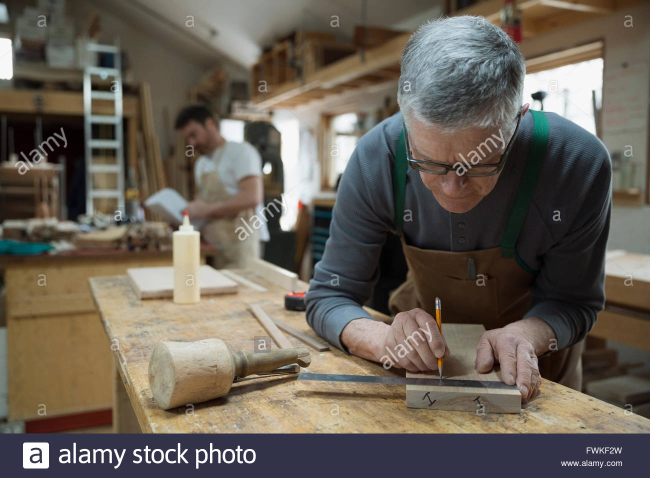 Carpenter measuring and marking wood piece in workshop - Stock Image
