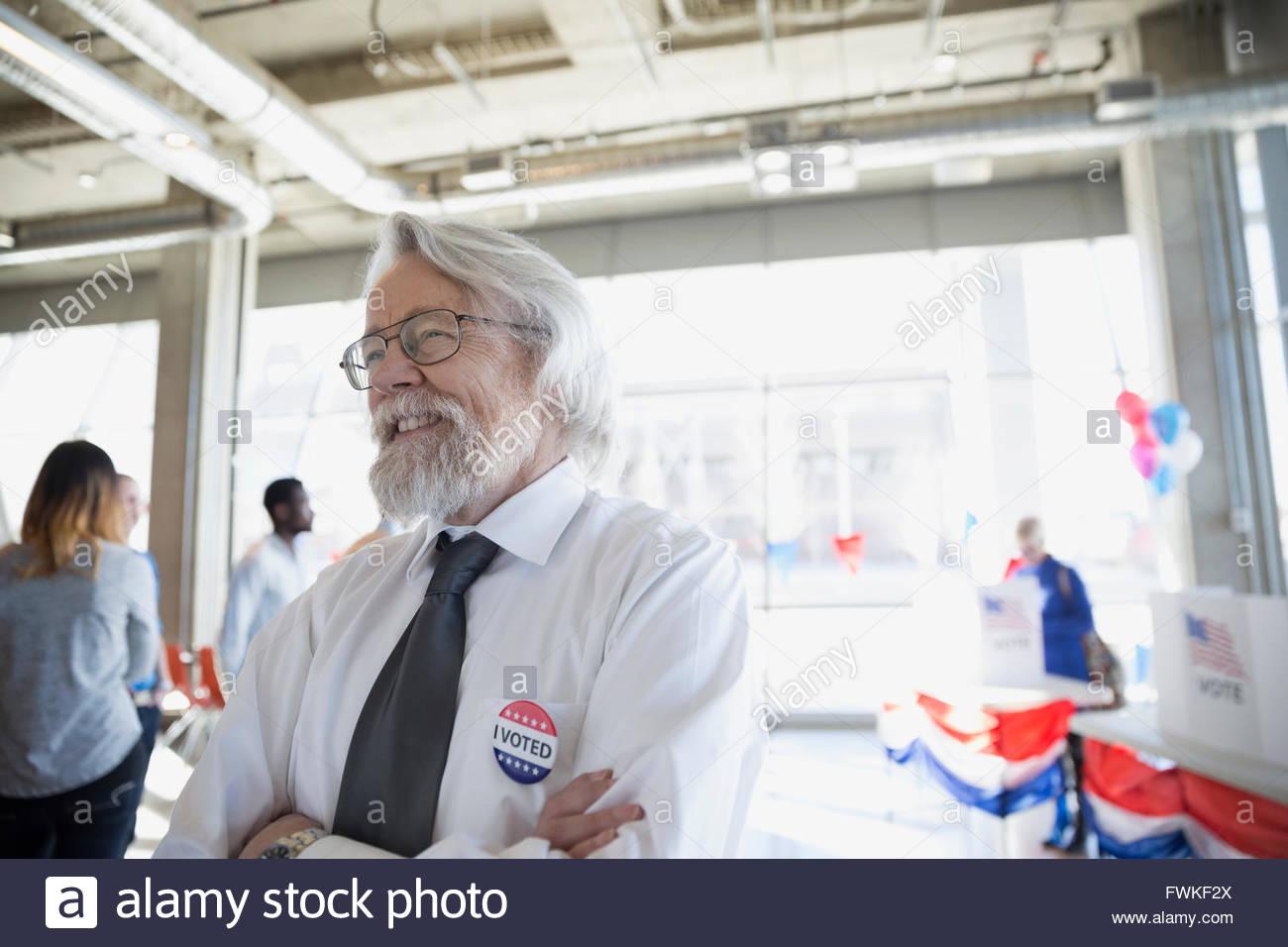 Smiling senior man at voter polling place - Stock Image