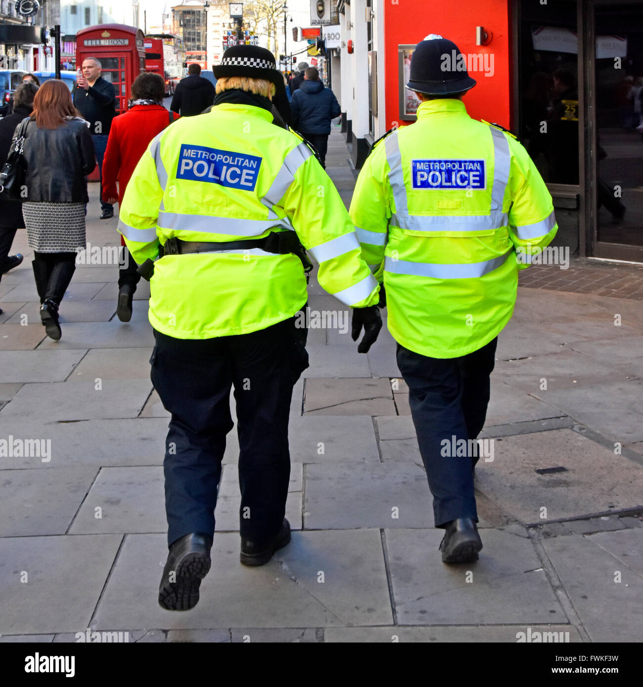 Back view female Metropolitan Police officer in distinctive cap (left) & male officer traditional helmet patrolling - Stock Image