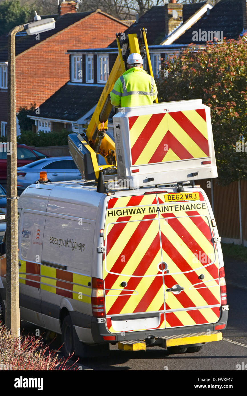 Contractor for Essex County Council worker high vis jacket on Cherry Picker hoist inspecting light fitting at top - Stock Image