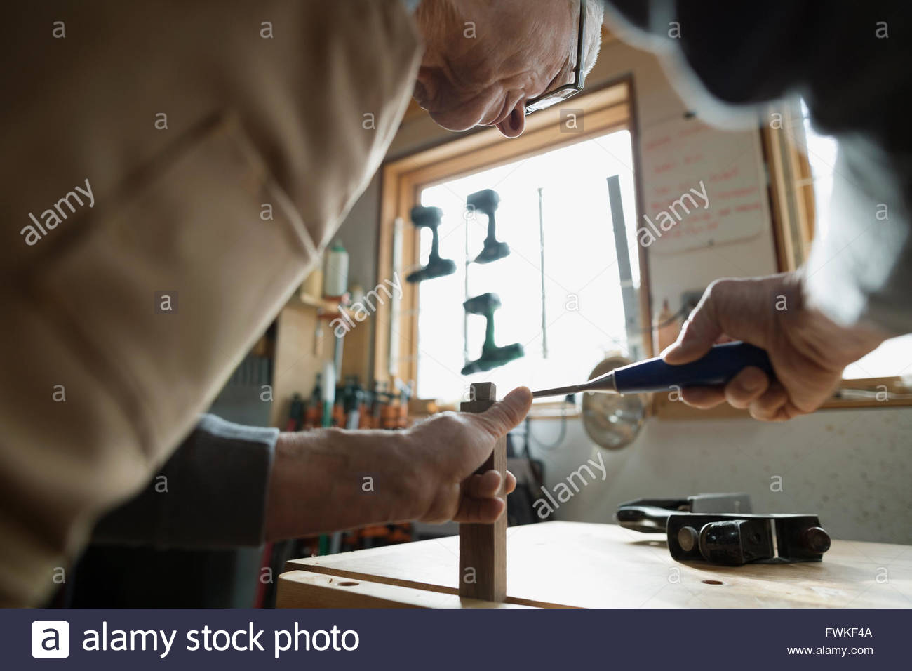 Carpenter using chisel on wood block in workshop - Stock Image