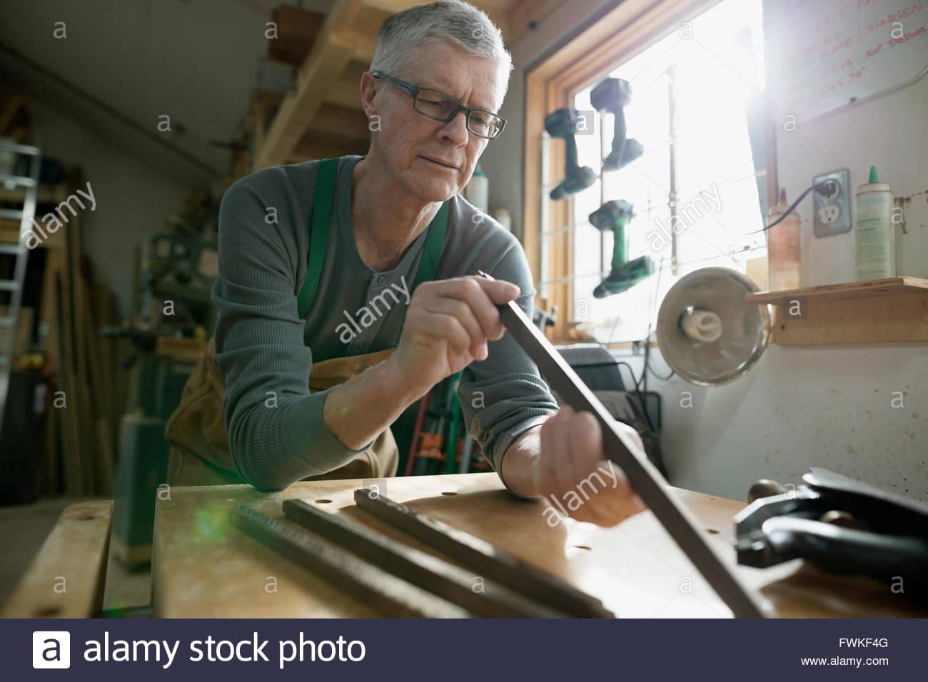 Carpenter examining tools in workshop - Stock Image