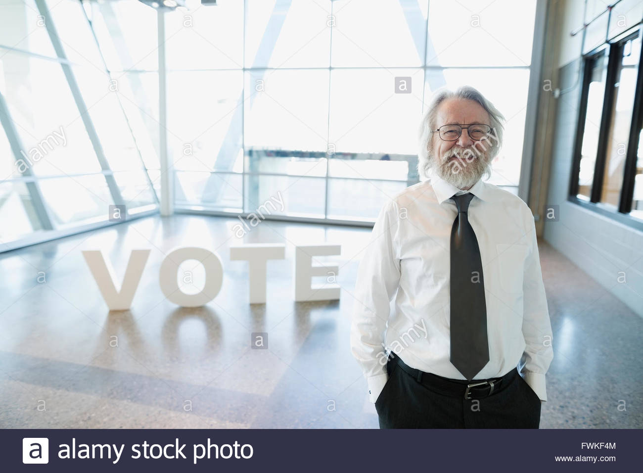 Portrait senior man in front of Vote text - Stock Image