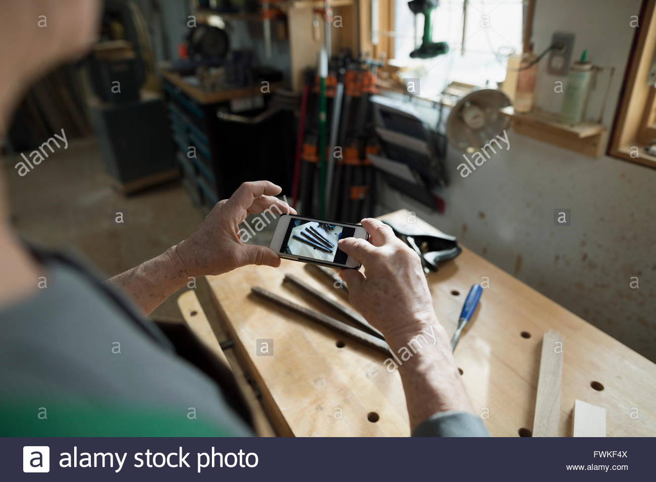 Carpenter photographing tools with camera phone in workshop - Stock Image