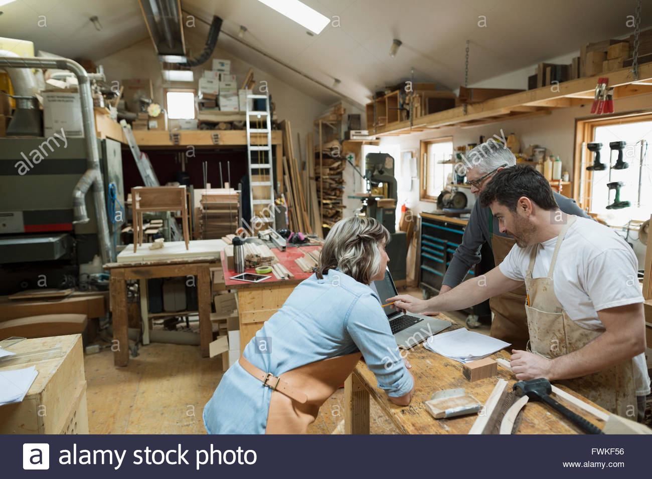 Carpenters using laptop in workshop - Stock Image