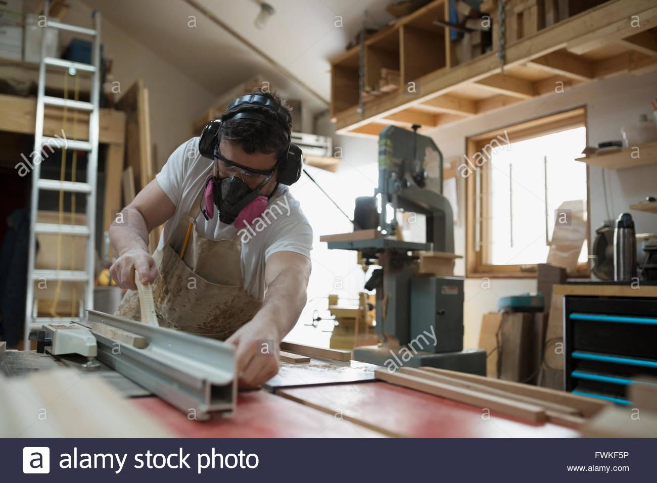 Carpenter wearing protective mask in workshop - Stock Image