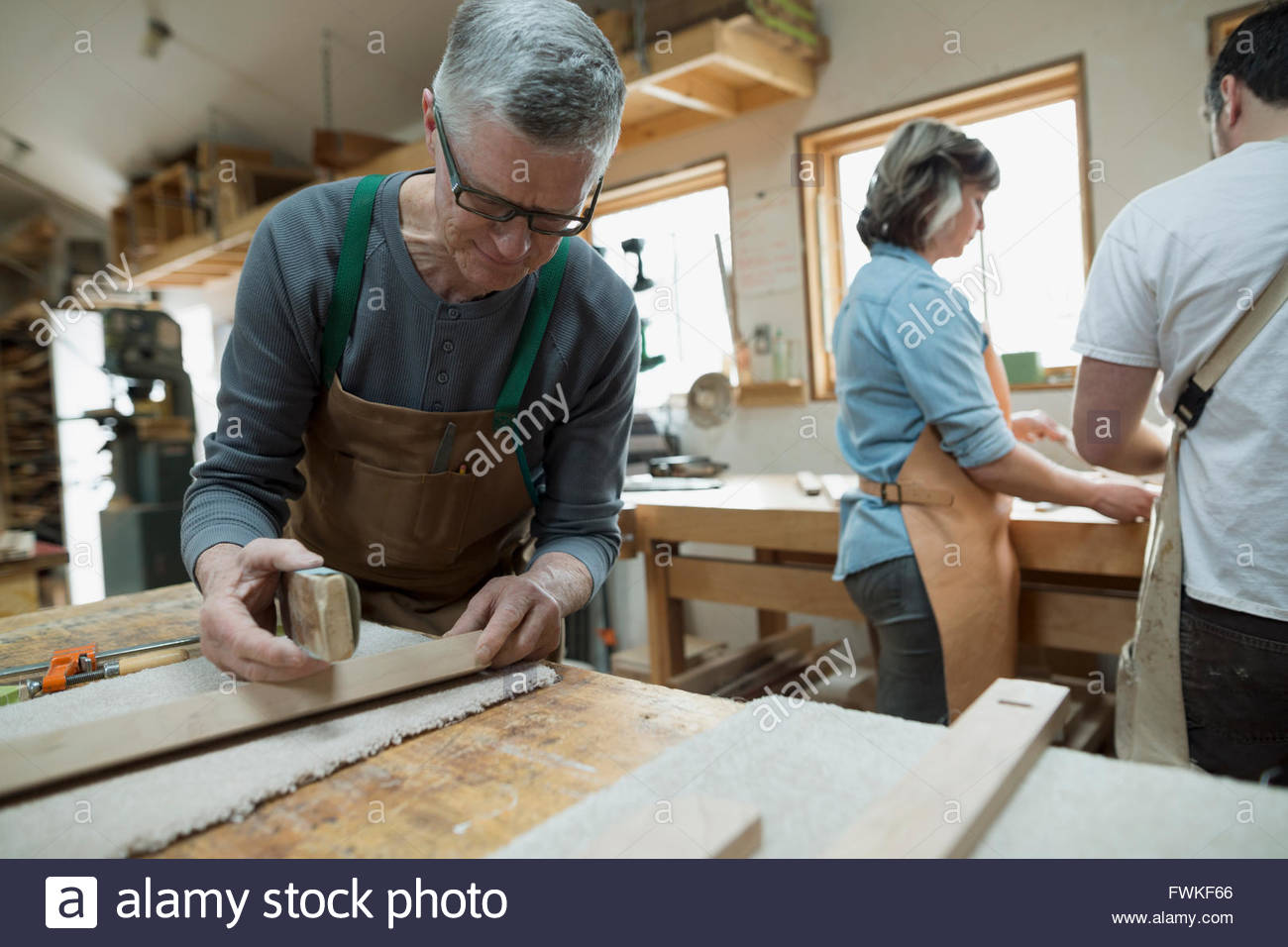Carpenter examining wood pieces in workshop - Stock Image