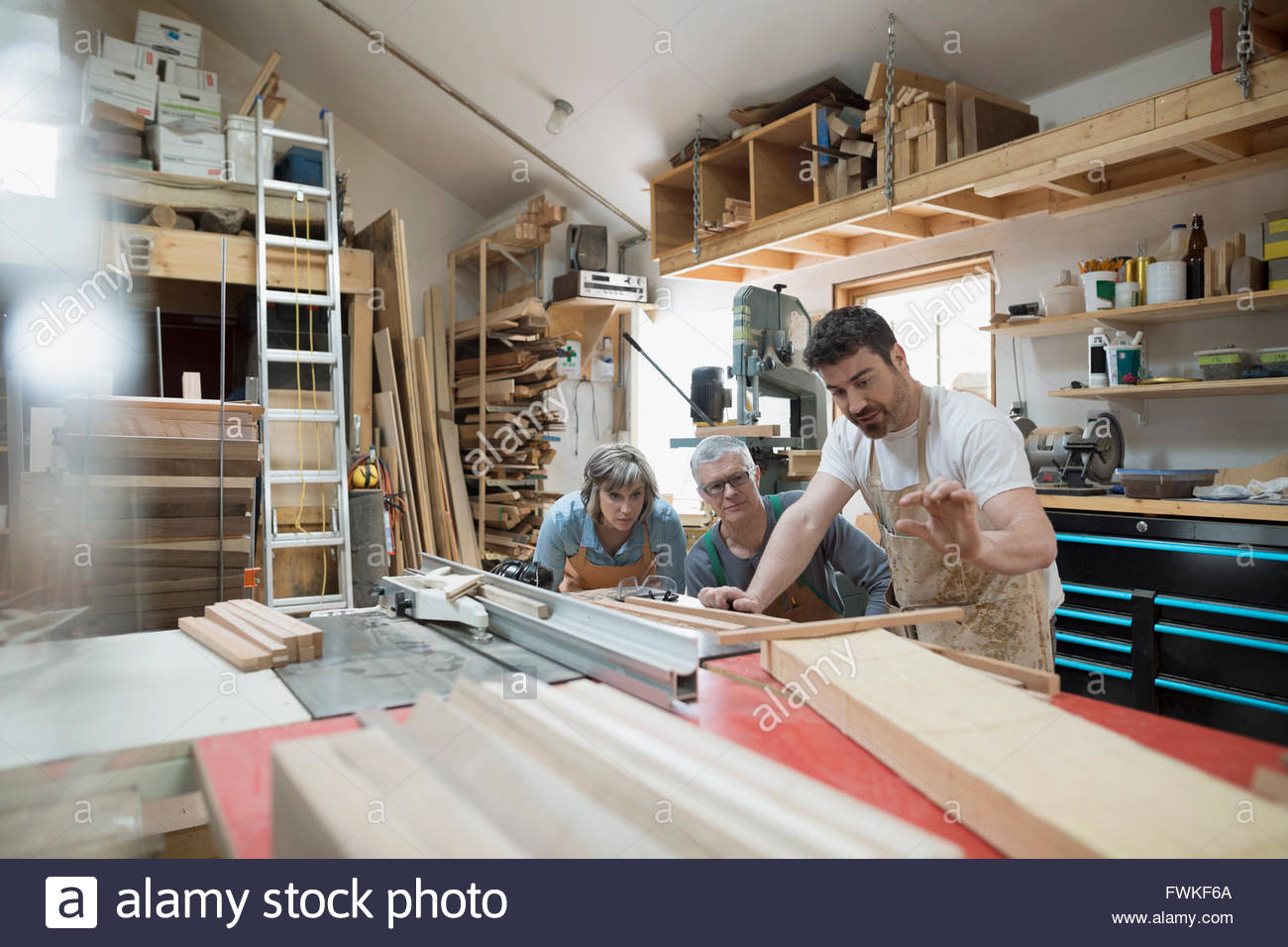 Carpenters discussing wood plank in workshop - Stock Image