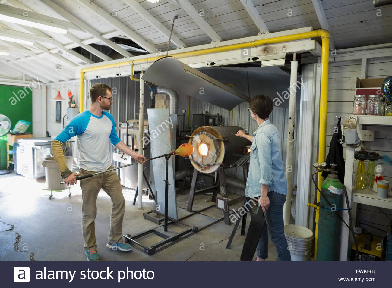 Glassblower heating molten glass at furnace in workshop - Stock Image