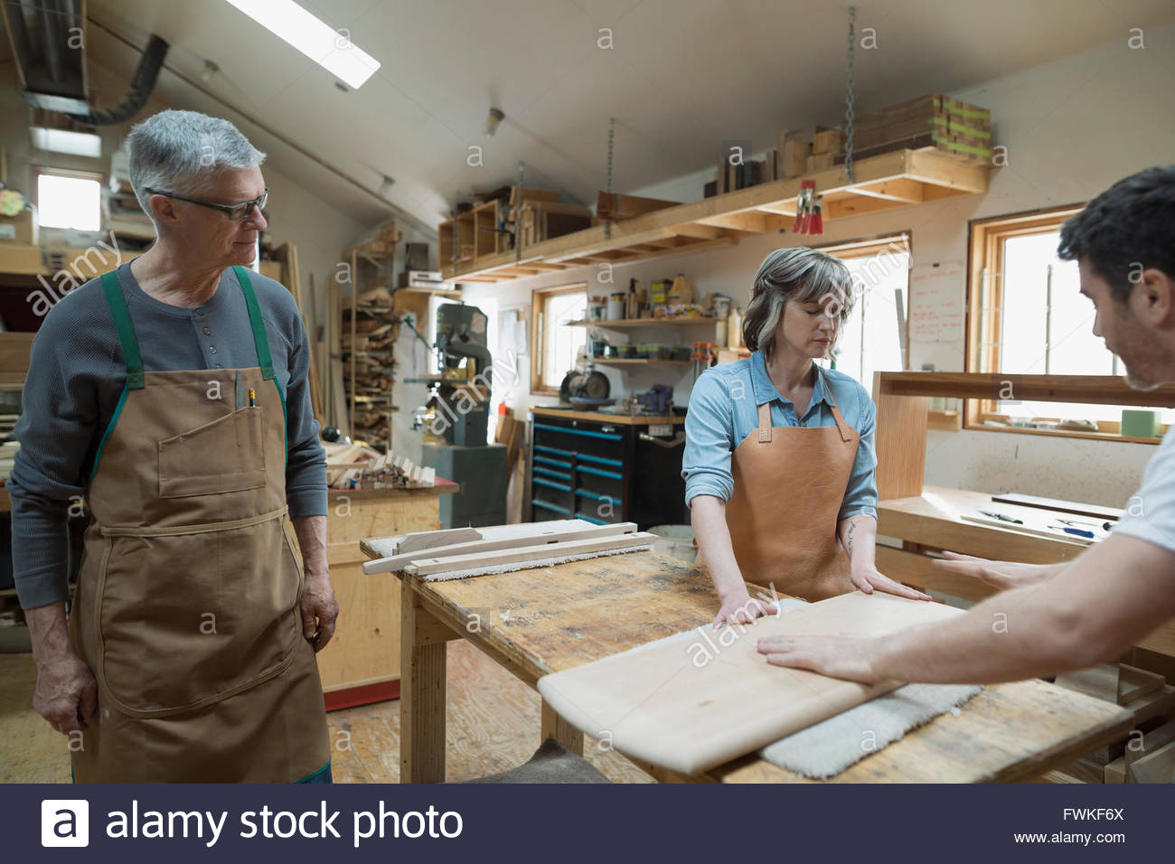 Carpenters examining wood pieces in workshop - Stock Image