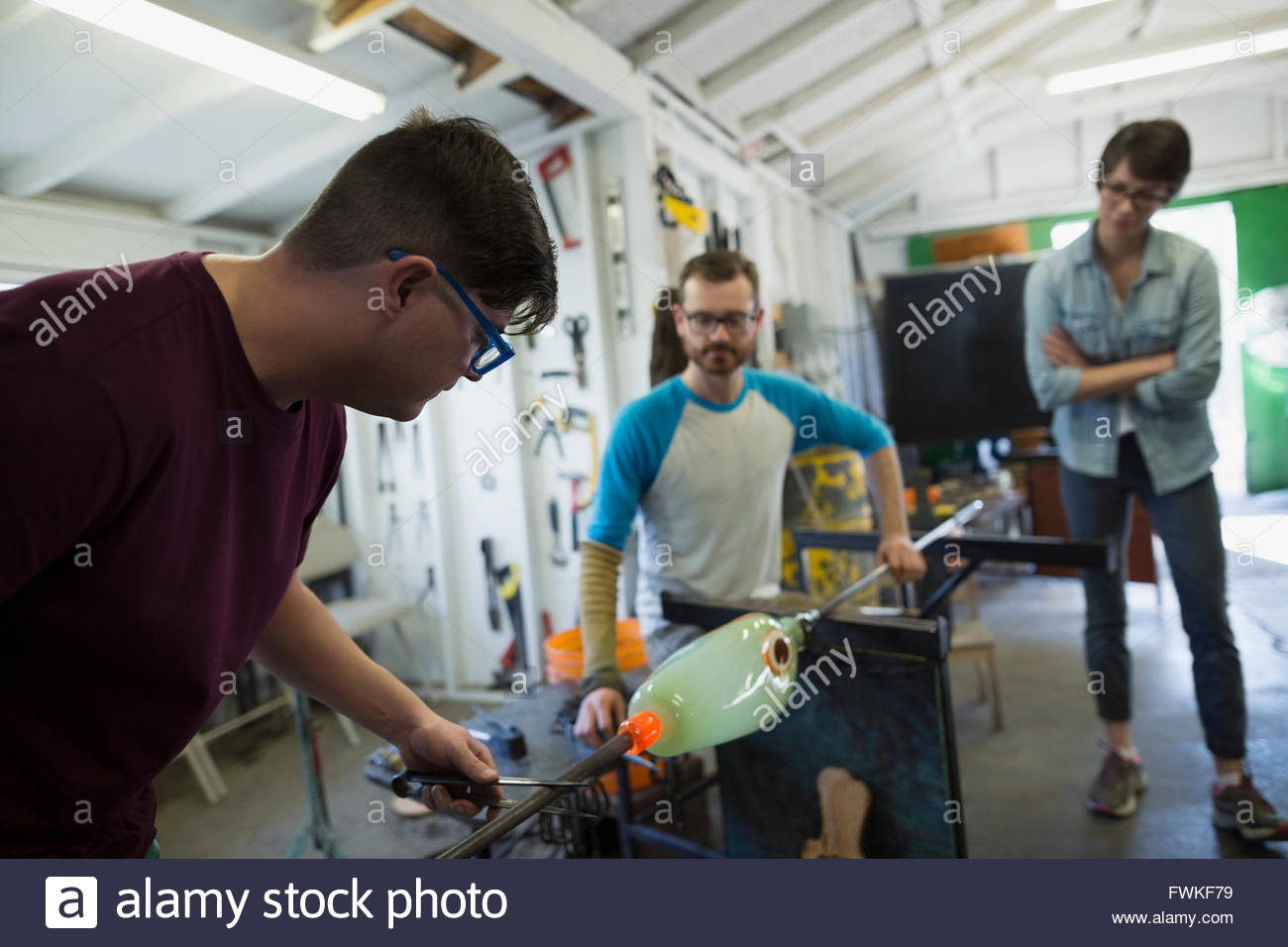 Glassblowers shaping molten glass in workshop - Stock Image