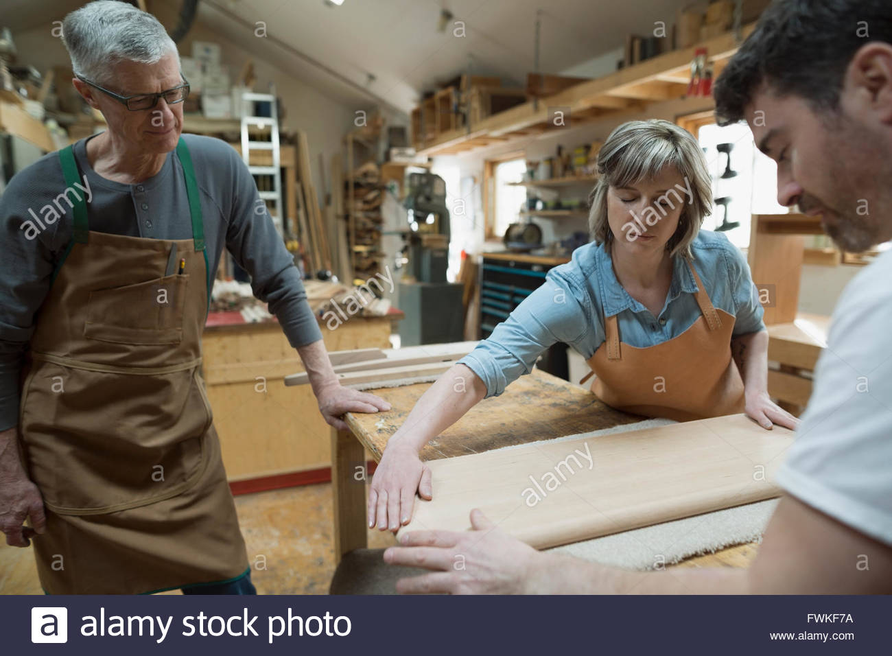 Carpenters examining wood piece in workshop - Stock Image
