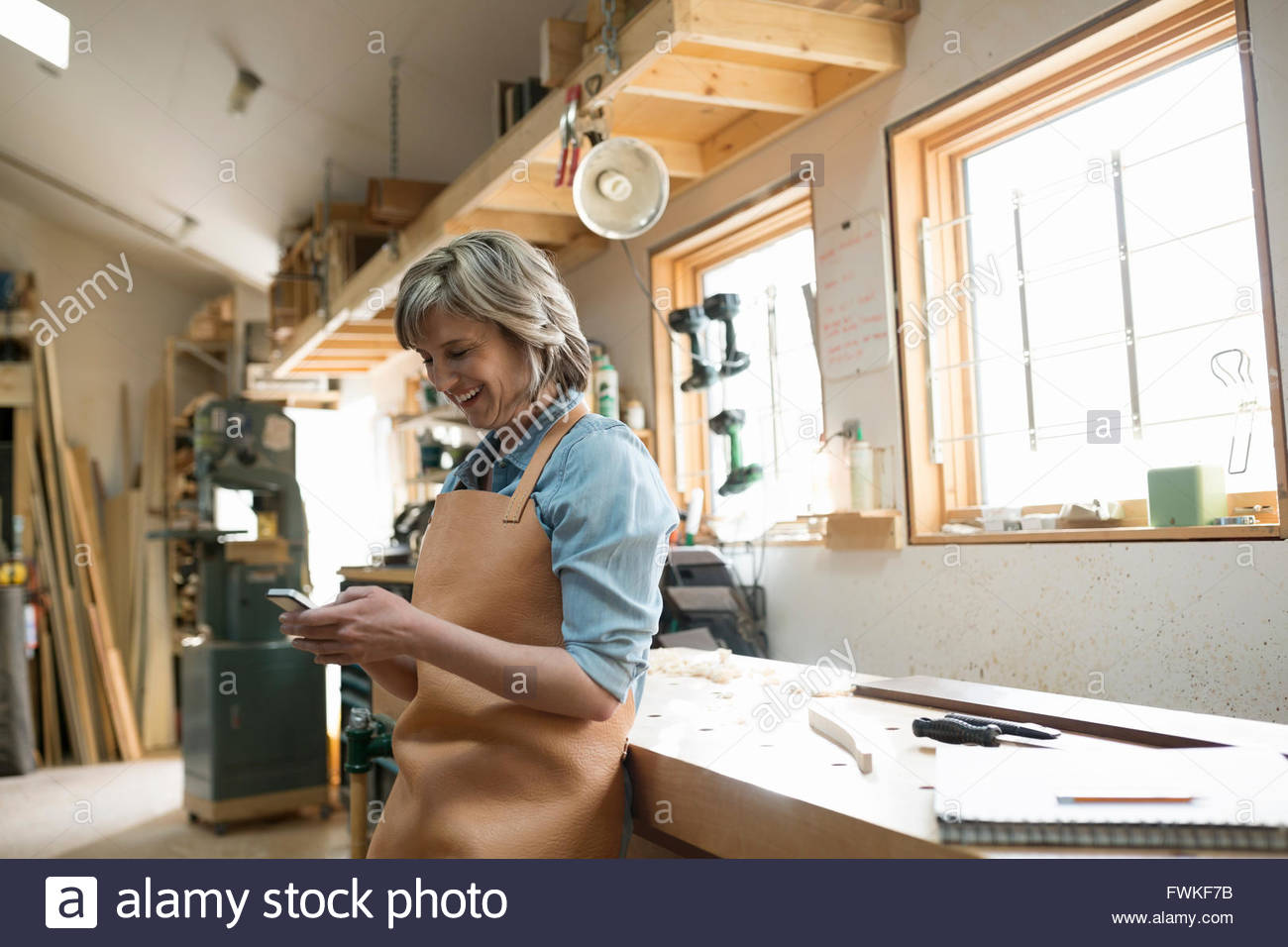 Smiling female carpenter using cell phone in workshop - Stock Image