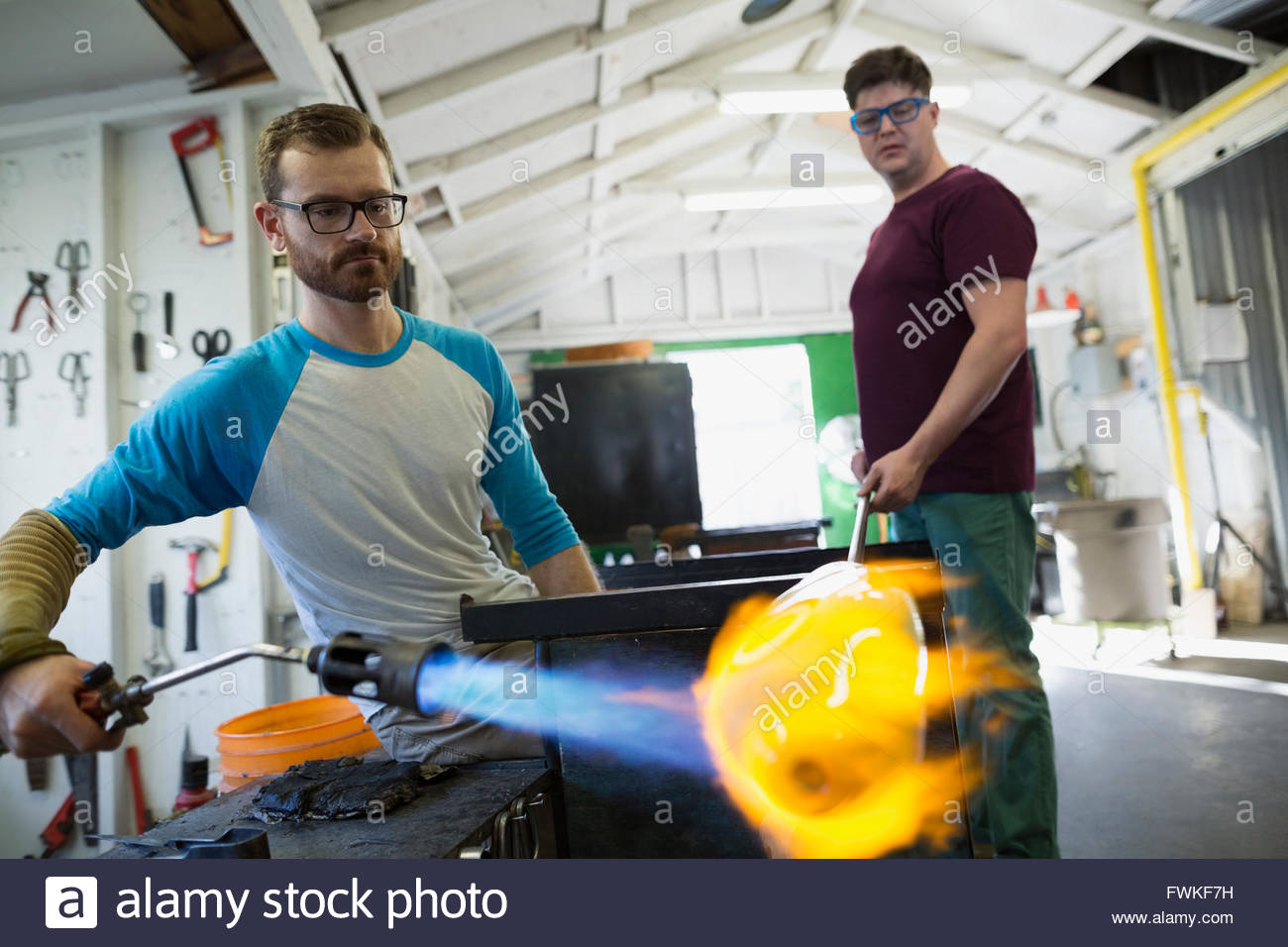 Glassblowers heating molten glass with torch in workshop - Stock Image