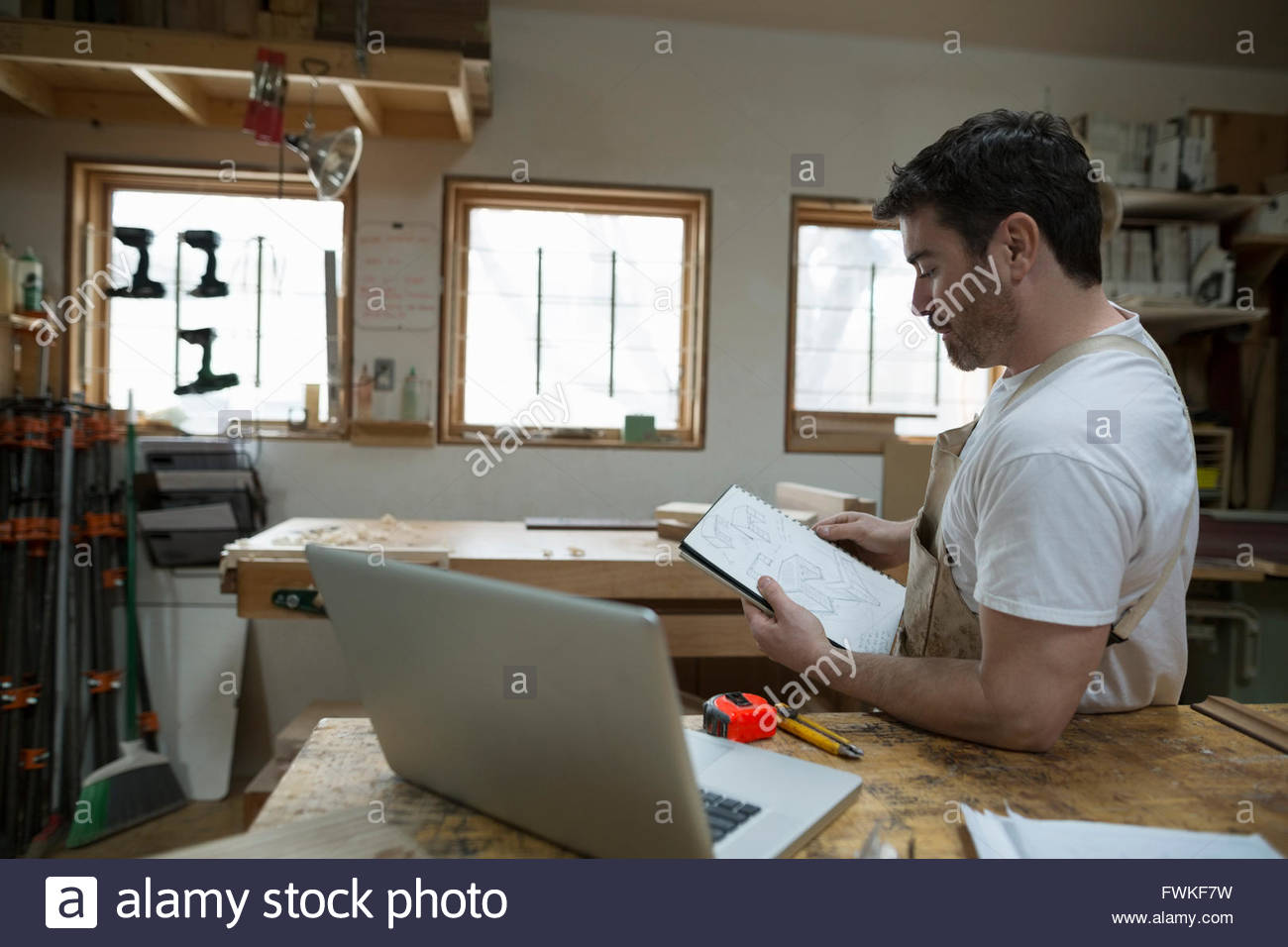 Carpenter brainstorming and sketching in workshop - Stock Image