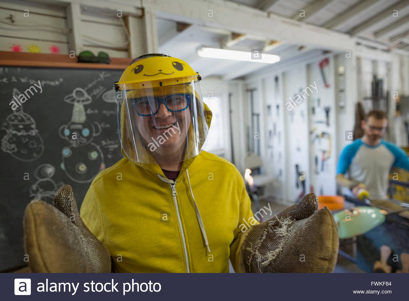 Portrait smiling glassblower in protective workwear and gloves - Stock Image