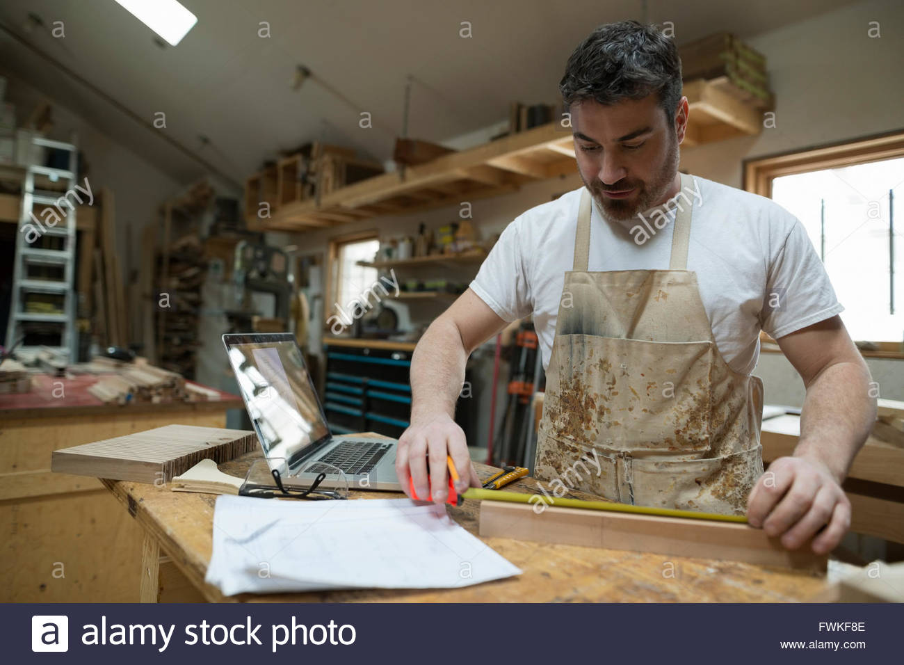 Carpenter measuring wood block in workshop - Stock Image