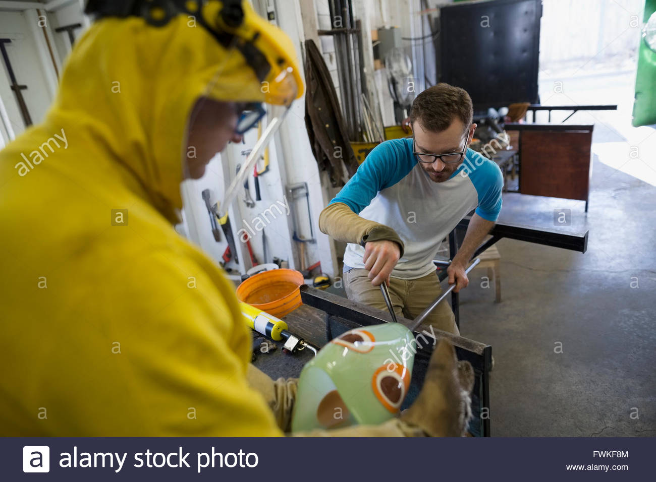 Glassblowers shaping glass in workshop - Stock Image