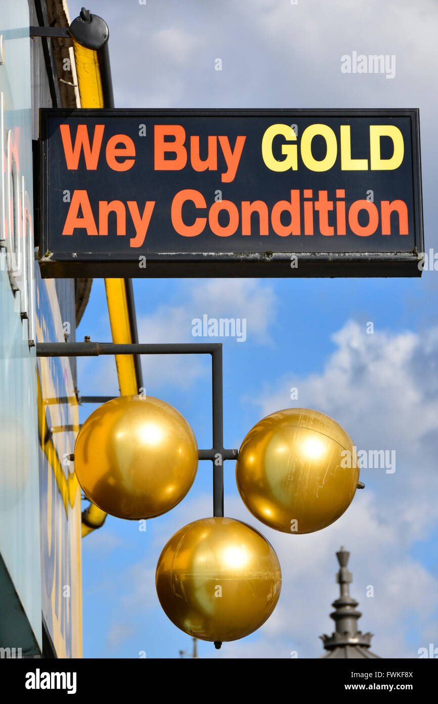 We Buy Gold sign above pawnbroker shop gold balls symbol in Barking high street in London borough of Barking and - Stock Image