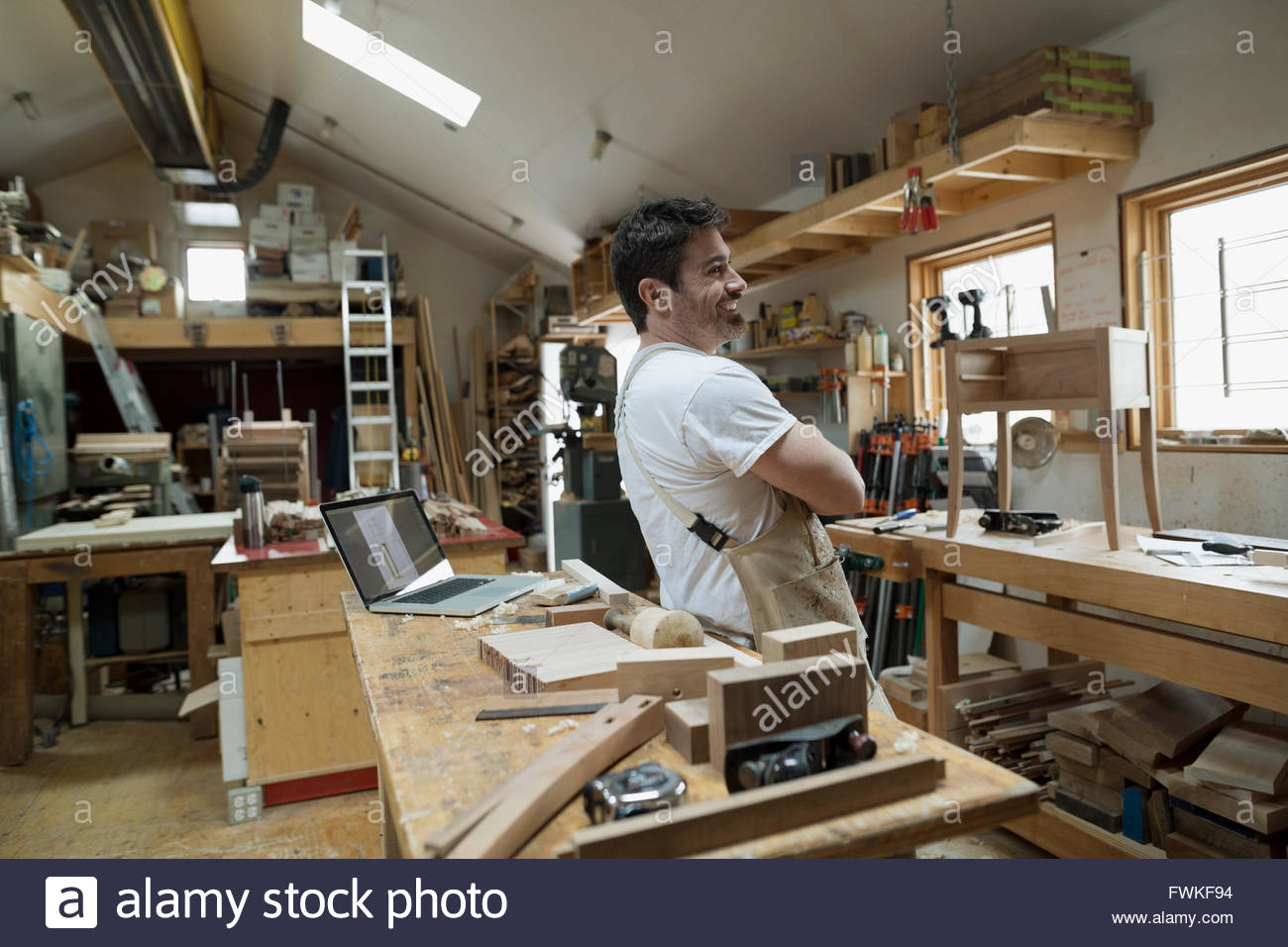 Confident carpenter with arms crossed in workshop - Stock Image