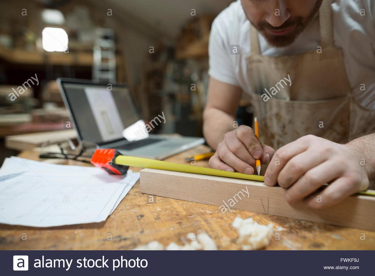 Carpenter measuring wood block in workshop - Stock Image