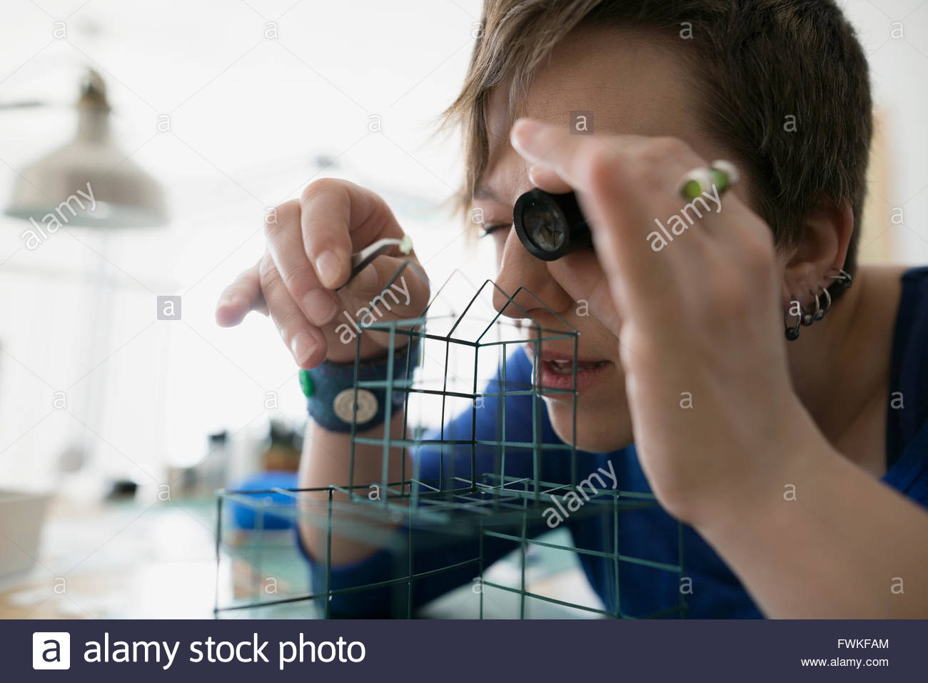 Craftswoman using loupe to assemble wire cage - Stock Image