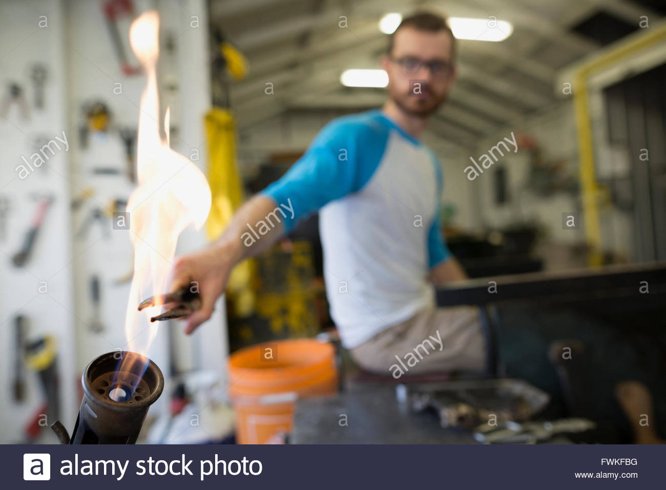 Glassblower heating tongs in flame - Stock Image