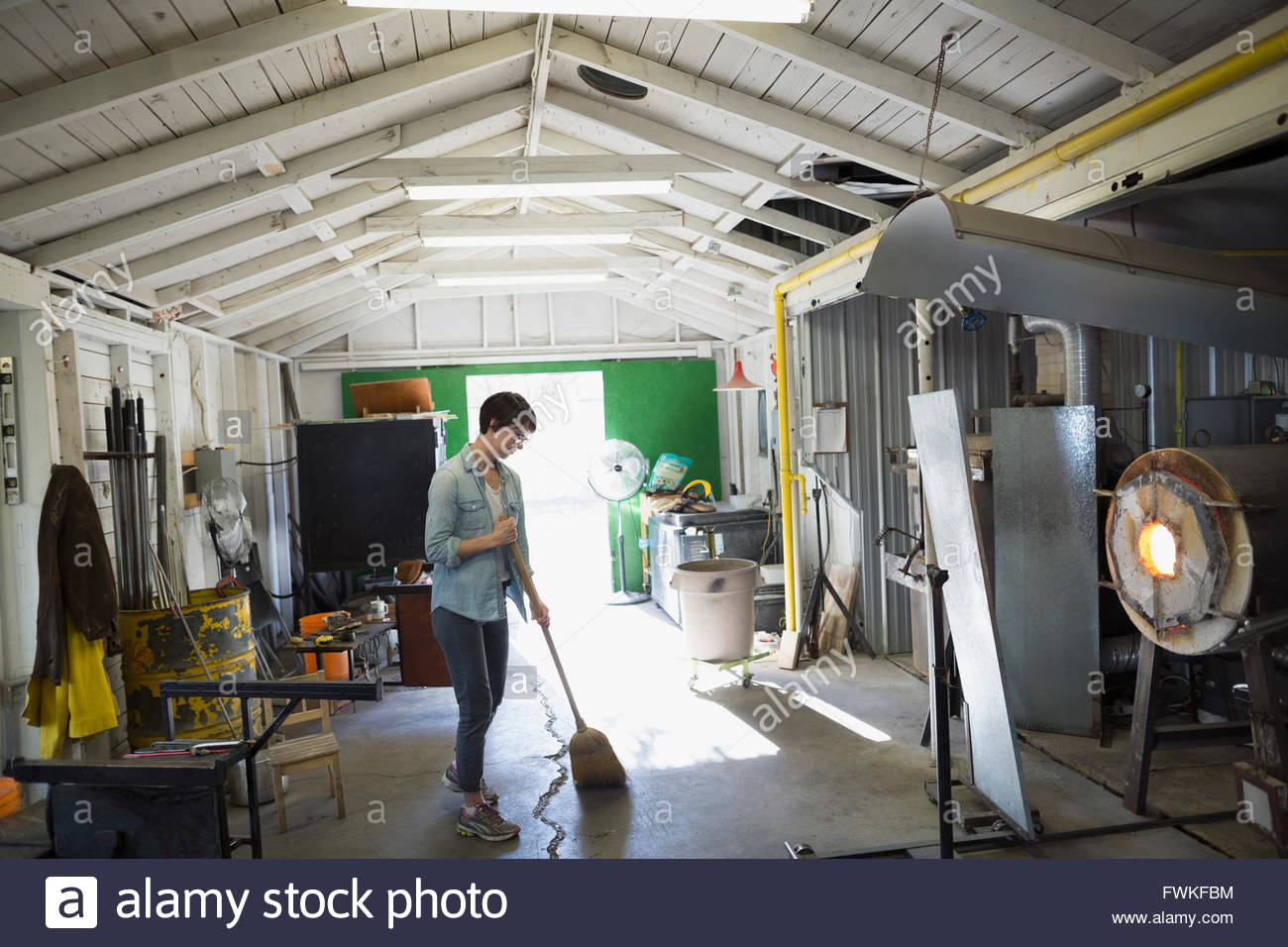 Female glassblower sweeping in workshop - Stock Image