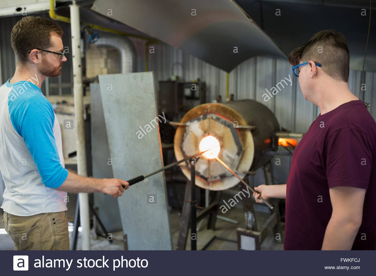 Glassblowers heating rods at furnace in workshop - Stock Image
