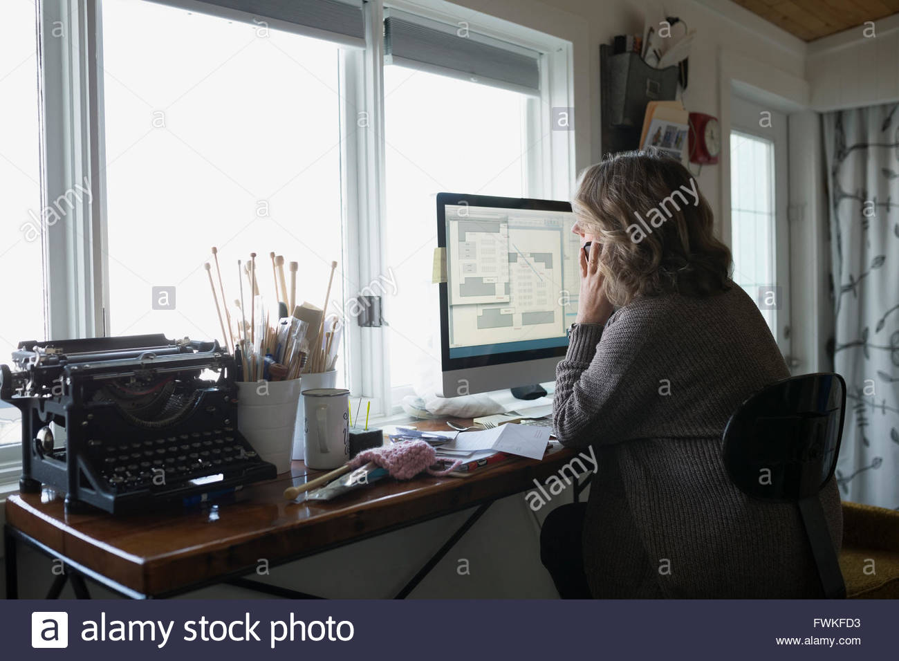 Yarn store owner working desk talking cell phone - Stock Image